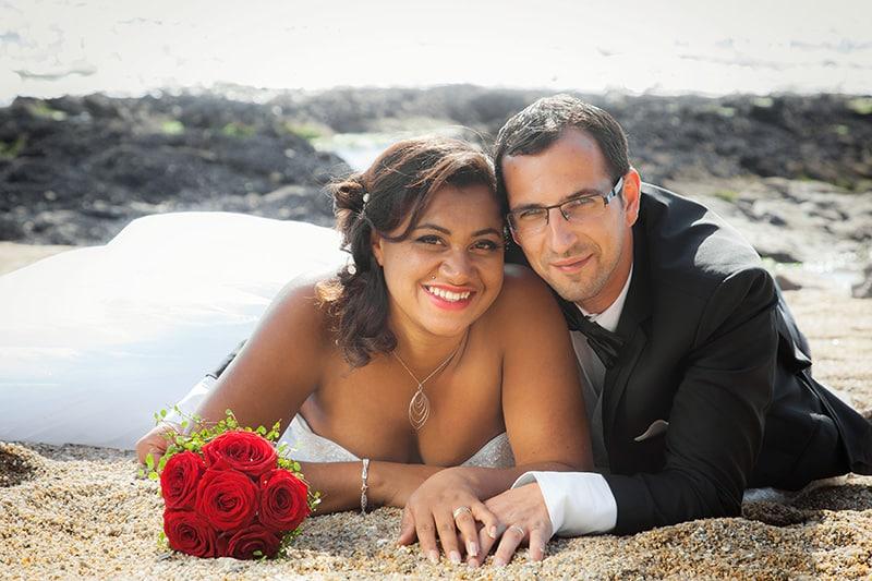photo de mariés allongés sur le sable