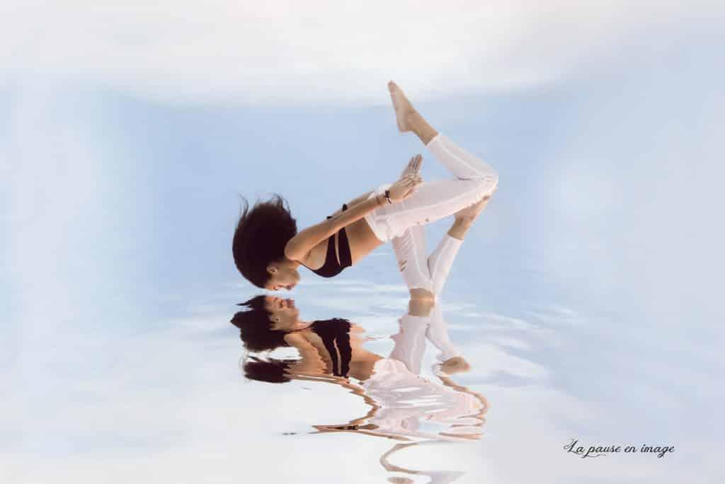 Une séance photo en piscine sous l'eau, jeune fille métisse en pantalon blanc avec un haut de maillot de bain noir. Reflet de la personne à la surface de l'eau