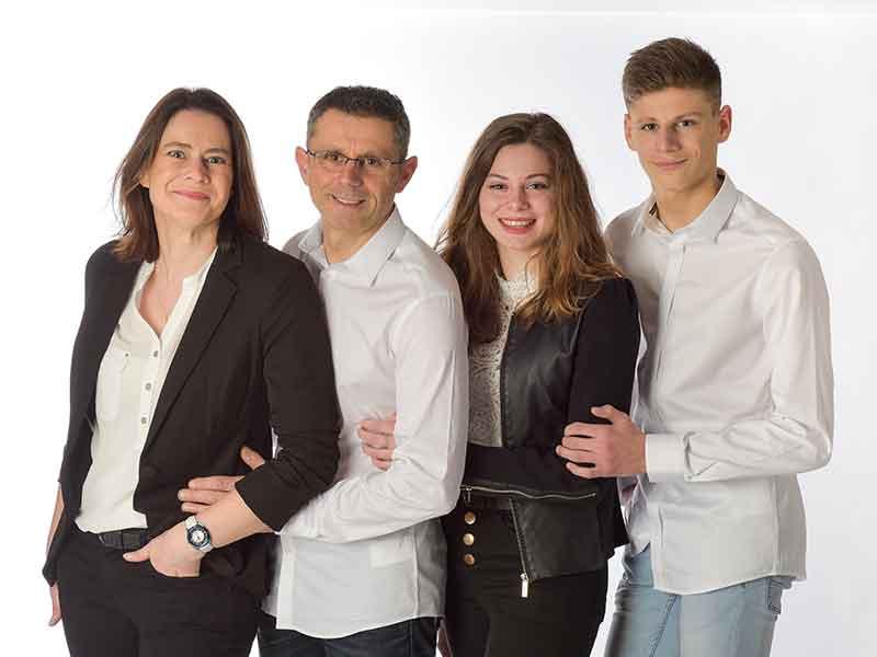 photo de famille 1 couple avec 2 ados studio fond blanc chemise blanche pour les hommes et chemisier blanc pour les femmes avec une veste noir expression souriante