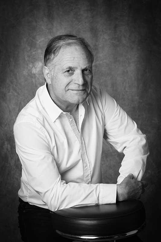 portrait d'un homme en studio sur fond gris photo en noir et blanc porte une chemise blanche