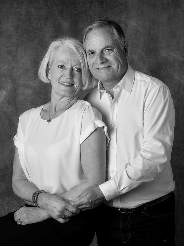 photo en studio d'un couple vêtu de blanc sur fond gris photo en noir et blanc